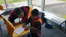 Students at Alexander Elementary working together on a writing prompt