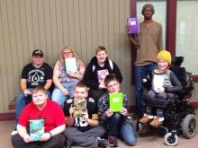 Students sit on the ground displaying their journals from Freedom Words.