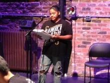 Student performs her poetry on stage.