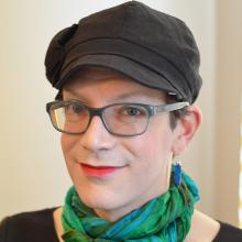 Stephanie Burt is wearing blue glasses, red lipstick, a green scarf, and a grey hat.