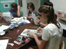 Students sit around a table and create their image and word journals.