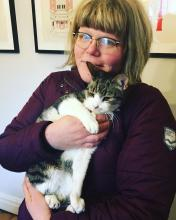 Katie, wearing bangs, round glasses, and a black turtleneck, is holding a white and gray cat.