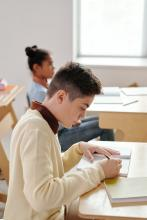 A teen sitting at a classroom desk writing in a notebook